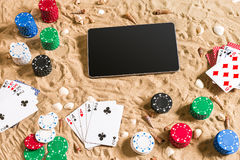 Gambling on vacation concept - white sand with seashells , colored poker chips and cards. Top view. Copy space. Summer Royalty Free Stock Photo