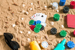 Gambling on vacation concept - white sand with seashells , colored poker chips and cards. Top view. Copy space. Summer Stock Images