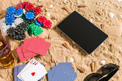 Gambling on vacation concept - white sand with seashells , colored poker chips and cards. Top view Royalty Free Stock Image