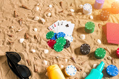 Gambling on vacation concept - white sand with seashells , colored poker chips and cards. Top view. Copy space. Summer. Sun flare Royalty Free Stock Photo