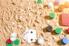 Gambling on vacation concept - white sand with seashells , colored poker chips and cards. Top view. Copy space. Summer. Sun flare Stock Photography