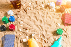 Gambling on vacation concept - white sand with seashells , colored poker chips and cards. Top view. Copy space. Summer. Sun flare Stock Image