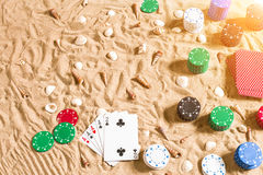 Gambling on vacation concept - white sand with seashells , colored poker chips and cards. Top view Royalty Free Stock Photography
