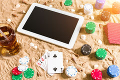 Gambling on vacation concept - white sand with seashells , colored poker chips and cards. Top view Stock Photos