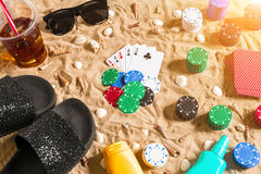 Gambling on vacation concept - white sand with seashells , colored poker chips and cards. Top view Stock Image