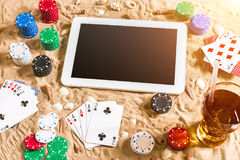 Gambling on vacation concept - white sand with seashells , colored poker chips and cards. Top view Stock Photography