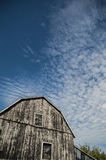Gambrel roof black weathered barn with deep blue sky and cloudsc Stock Photography
