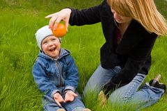 Game. Mum with the son play on a grass with an orange, they are dared Royalty Free Stock Image