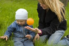 Game. Mum with the son play on a grass with an orange, they are dared Royalty Free Stock Photos