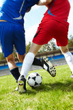 During game. Vertical image of soccer ball on the field with footballers legs trying to kick it Royalty Free Stock Photo