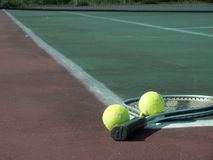 After the game. Tennis racket and two balls lying on the court royalty free stock photography