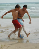 Game on!3. Playing soccer on the beach Royalty Free Stock Photo