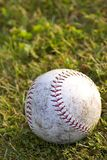 After the Game. A worn softball laying on the grass stock image