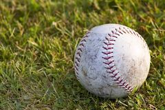 After the Game. A worn softball lying in the grass royalty free stock photos