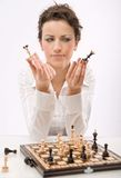 Game. A young woman holding chess pieces royalty free stock photo