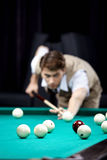 Game in billiards. The young attractive well dressed man plays billiards Royalty Free Stock Image