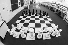 The Game. ON BOARD OF CRUISE SHIP N.C.L. DAWN JAN 26 2016: Chessboard and chess pieces on the deck Royalty Free Stock Photos