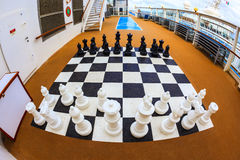 The Game. ON BOARD OF CRUISE SHIP N.C.L. DAWN JAN 26 2016: Chessboard and chess pieces on the deck Stock Photos