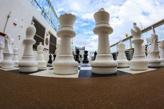 The Game. ON BOARD OF CRUISE SHIP N.C.L. DAWN JAN 26 2016: Chessboard and chess pieces on the deck Royalty Free Stock Photo