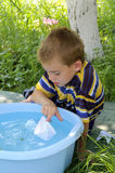 Game with the boat. Small boy plays with the paper ship in fresh air Royalty Free Stock Photography
