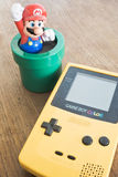 Game Boy Color device with Super Mario Bros figure Royalty Free Stock Photos