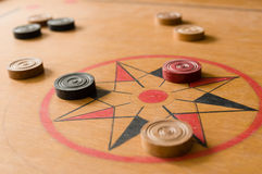 A game of carrom with scattered stones on the board around the center star Royalty Free Stock Images
