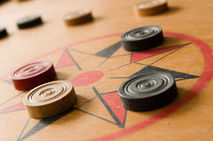 A game of carrom with scattered stones on the board around the center star Royalty Free Stock Image