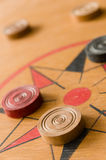 A game of carrom with scattered stones on the board around the center star Royalty Free Stock Photo