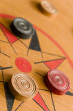A game of carrom with scattered stones on the board around the center star Stock Photo