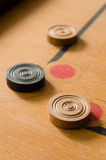 A game of carrom with scattered stones at a corner of the board Royalty Free Stock Photography