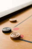 A game of carrom with scattered stones at a corner of the board Royalty Free Stock Images