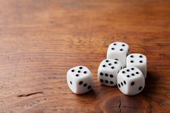 Game of chance concept. Gambling devices. White dice on rustic wooden board. Copy space for text. stock images