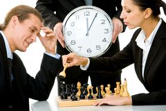 Game of chess. Image of businessman and businesswoman playing chess with businessman holding clock on background Stock Photos