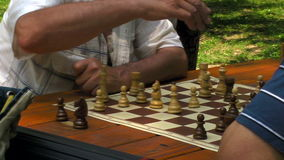Game of chess. Active retired people, two senior men playing chess at park stock footage