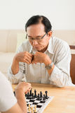 Game of chess. Aged Vietnamese men thinking about next move in game of chess royalty free stock photo
