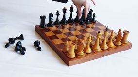 Game of chess. The hand puts the black pieces on the chessboard. Game of chess stock video