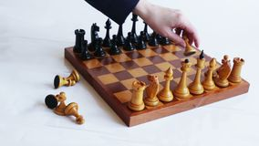Game of chess. The hand puts the white pieces on the chessboard. Game of chess stock footage