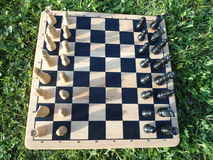 A game of chess outdoors. Wooden chess board with chess pieces, playing a game of chess outdoors Royalty Free Stock Images