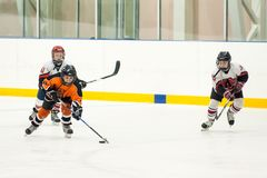 Game between children ice-hockey teams Stock Photos