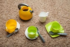 Game children`s tea ceremony from colorful toy utensils stock photos