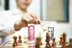 A game between CNY and USD. U.S. Dollar USD and Chinese Yuan CNY or RMB bills on a chess board, concept for currency games Stock Image