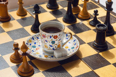Game concept. Cup of hot coffee on chessboard with wooden figure. Royalty Free Stock Photography