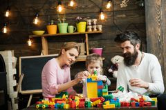 Game concept. Learning game. Son with mother and father play construction game. Little child learning through game.  royalty free stock image
