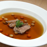 Game Consomme. Delicious game consomme with poached quail breast and solferino garnish in a soup bowl Royalty Free Stock Photography