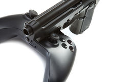 Game controller and handgun near it - studio close up shot. Virtual and real life concept Stock Photo