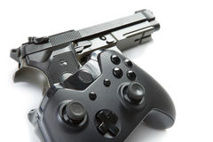 Game controller over a real handgun - studio close up shot. Virtual and real life concept Stock Images