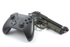 Game controller and a real handgun near it - studio shot. Virtual and real life concept Stock Photos