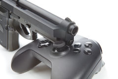 Game controller with real handgun near it - virtual and real life concept Stock Images