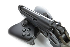 Game controller and a real handgun - studio close up shot. Virtual and real life concept Stock Photography