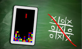 Game controller on tablet and ticktacktoe on chalkboard, concept Stock Photo